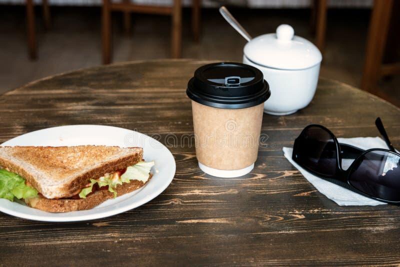 Almuerce con el bocadillo del triángulo, el café para llevar y gafas de sol en la tabla de madera imágenes de archivo libres de regalías