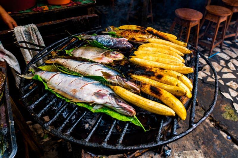 Almuerzo amazónico típico hecho en la parrilla, con los pescados y los plátanos imagenes de archivo