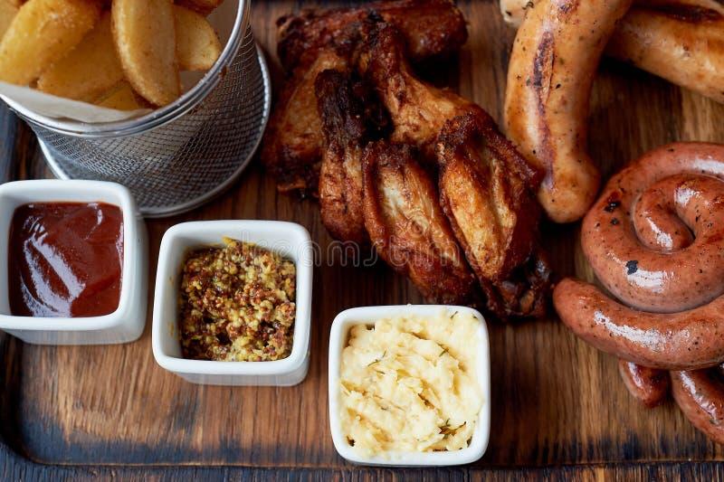 Almuerzo caluroso alemán en el pub Salchichas asadas a la parrilla, col guisada, cuscurrones, salsa Bocado de la cerveza fotografía de archivo libre de regalías
