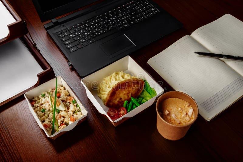 Almuerzo de negocios en la mesa de su ordenador fotos de archivo