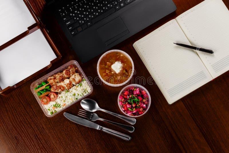 Almuerzo de negocios en la mesa de su ordenador fotos de archivo libres de regalías