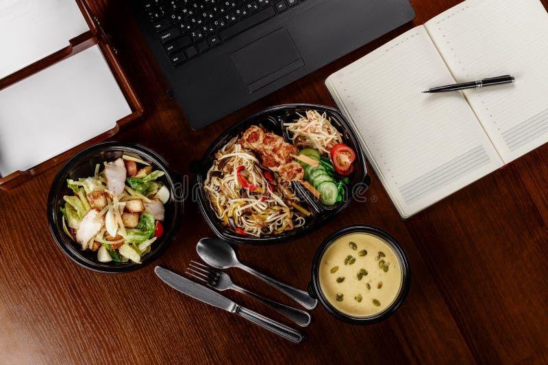 Almuerzo de negocios en la mesa de su ordenador imagenes de archivo
