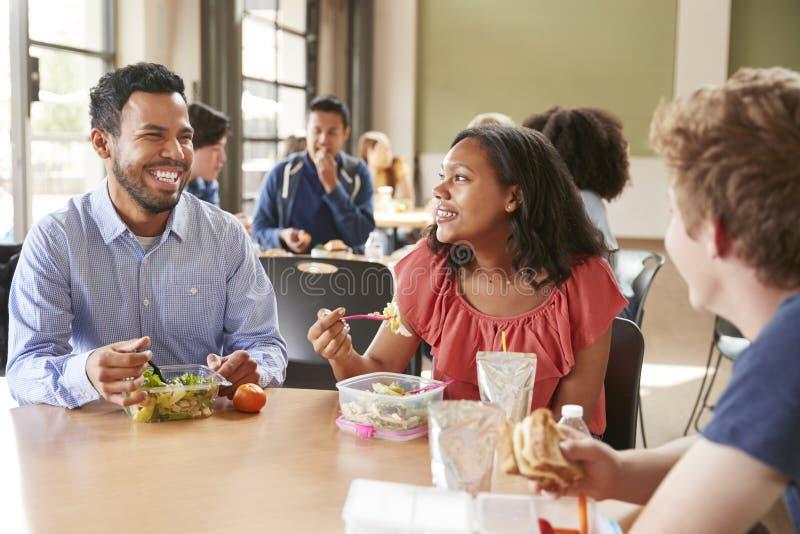 Almuerzo de And Students Eating del profesor en alta cafetería de la escuela durante hendidura fotografía de archivo libre de regalías