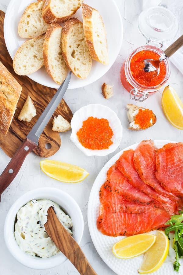 Almuerzo delicioso con los salmones salados, el caviar rojo, pan fresco y imagen de archivo
