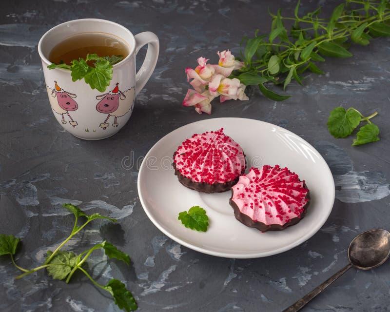 Almuerzo delicioso con té verde con la melcocha de la menta y de la cereza en chocolate en un platillo de cerámica fotografía de archivo