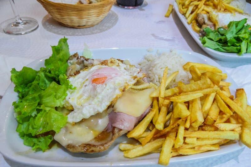 Almuerzo delicioso de la chuleta de cerdo, de patatas fritas y de la ensalada foto de archivo