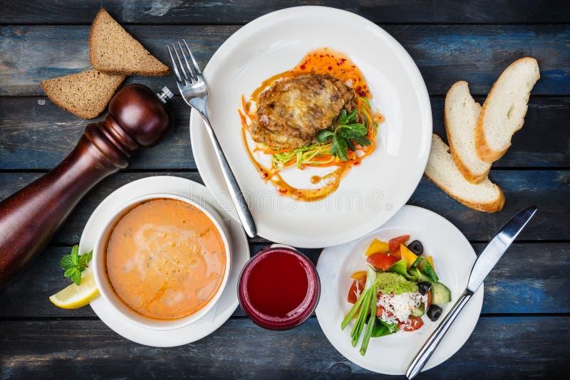 Almuerzo determinado típico Tajada del pollo, sopa de la calabaza y ensalada de las verduras, servidas con los cubiertos imagen de archivo