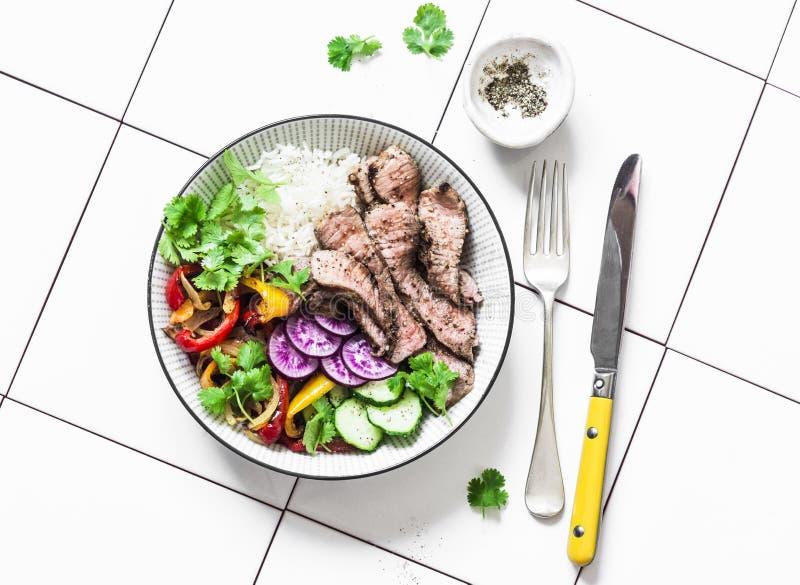 Almuerzo equilibrado - filete de carne de vaca, verduras y arroz asados a la parrilla en un fondo ligero, visión superior fotografía de archivo libre de regalías