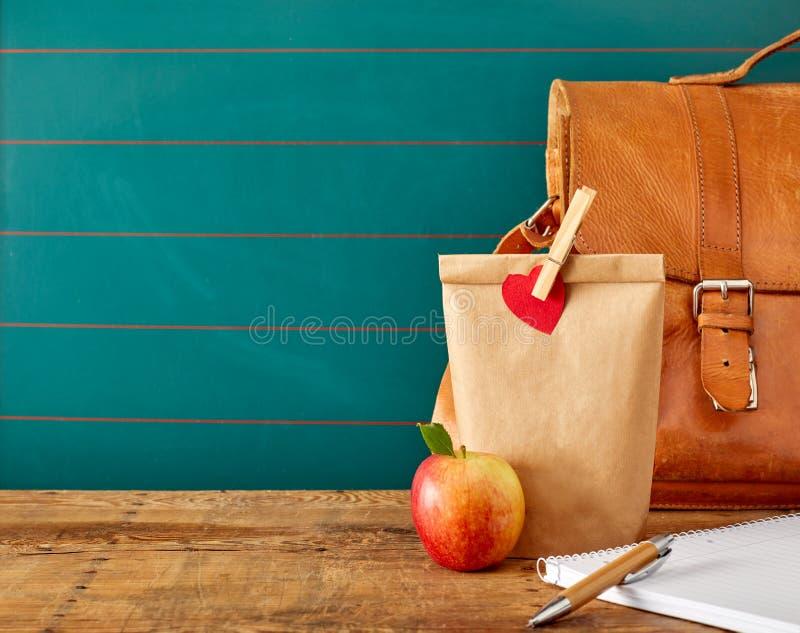 Almuerzo escolar con la cartera y el cuaderno imagenes de archivo