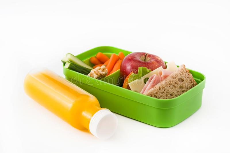 Almuerzo escolar sano: Bocadillo, verduras, fruta y jugo aislados imagenes de archivo