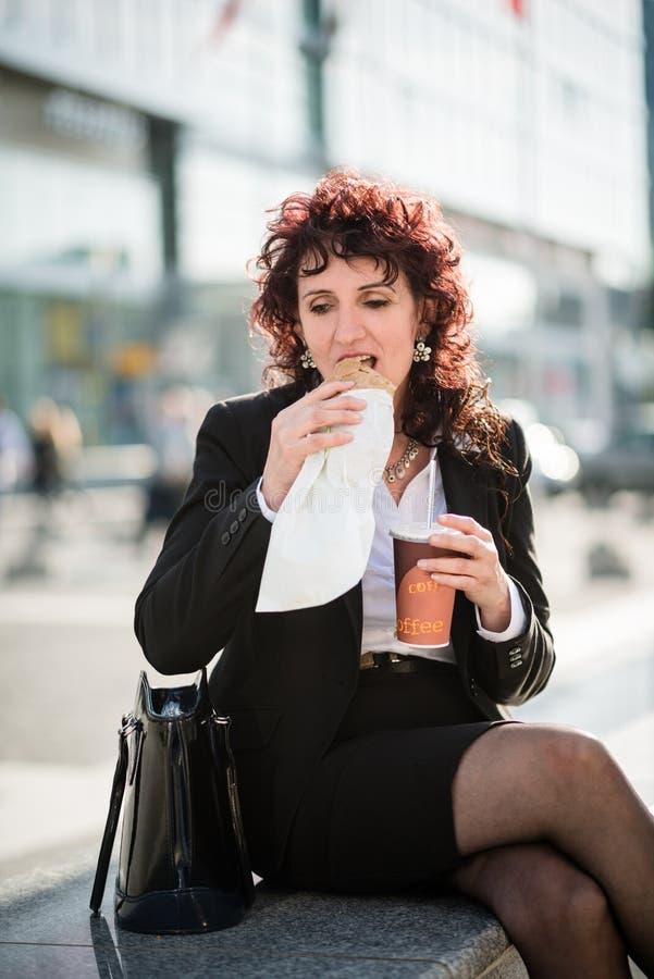 Almuerzo rápido - mujer de negocios que come en calle imagen de archivo