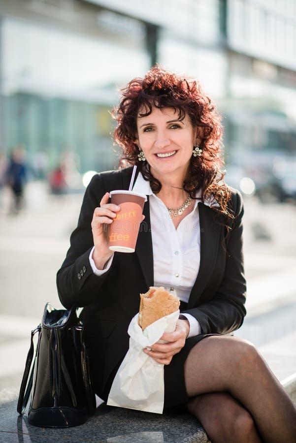 Almuerzo rápido - mujer de negocios que come en calle foto de archivo libre de regalías