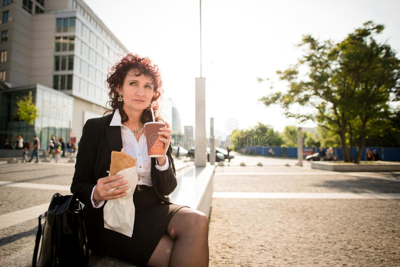 Almuerzo rápido - mujer de negocios que come en calle fotos de archivo