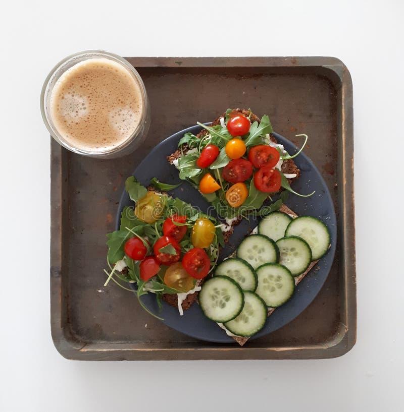 Almuerzo sano delicioso con la ensalada del pepino de los tomates de cereza del cohete de la tostada del pan de centeno y una taz foto de archivo libre de regalías