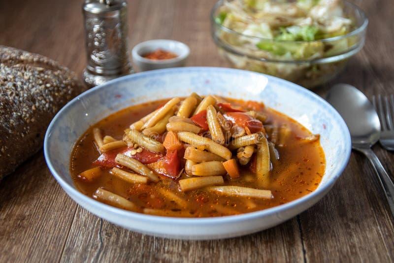 Almuerzo vegetariano Sopa de habas verdes con la salsa y las verduras de tomate imagen de archivo