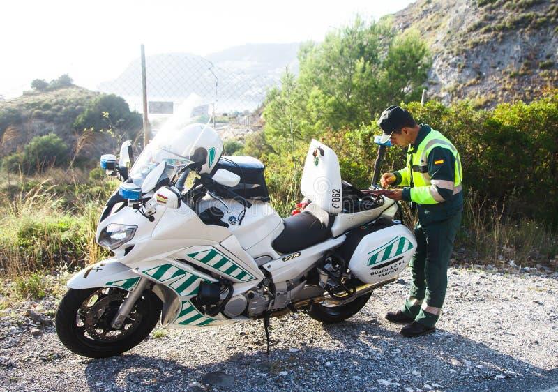 Almunecar, Hiszpański funkcjonariusz policji pisze bilecie dla motorowej obrazy Andalucia Hiszpania, Listopad - 3rd, 2018 - zdjęcia stock