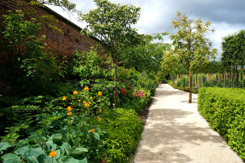 Alnwick garden pathway. The pathway in the ornamental garden of Alnwick Garden along a wall with roses and other flowers and plants royalty free stock photography