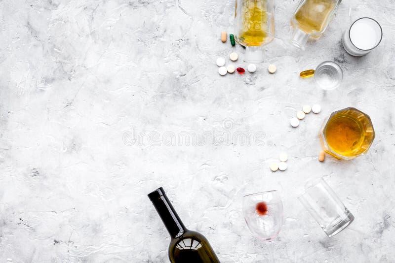 Alocohol恶习和酒精中毒治疗概念 玻璃、瓶和medcine药片在浅灰色的背景顶视图 免版税库存图片