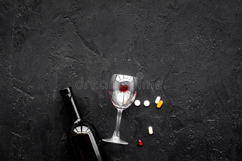 Alocohol恶习和酒精中毒治疗概念 玻璃、瓶和medcine药片在黑背景顶视图复制 免版税图库摄影