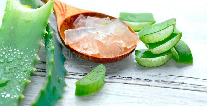 Aloe Vera gel closeup on white wooden background. Organic sliced aloevera leaf and gel, natural organic cosmetic ingredients royalty free stock photos
