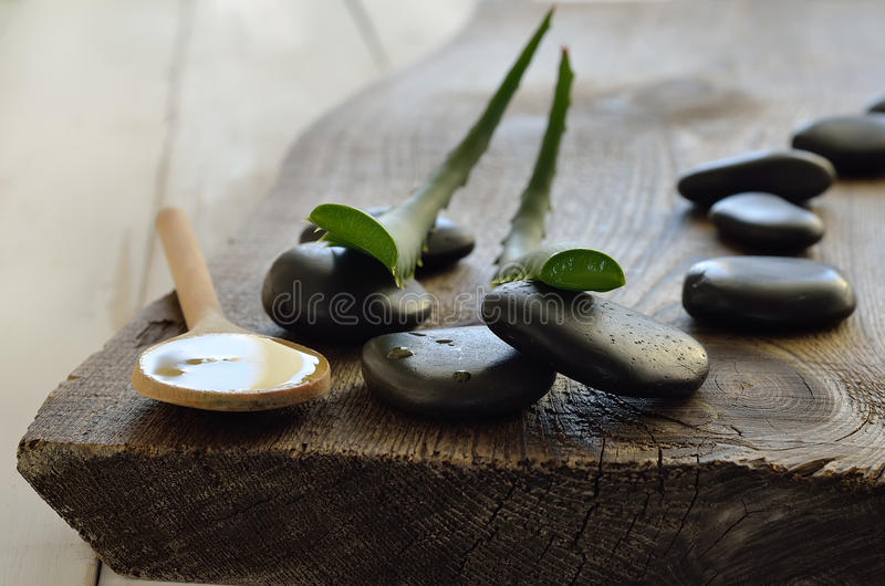 Aloe vera gel. And leaves on a wooden background. Spa set. Close up. Selective focus stock photography
