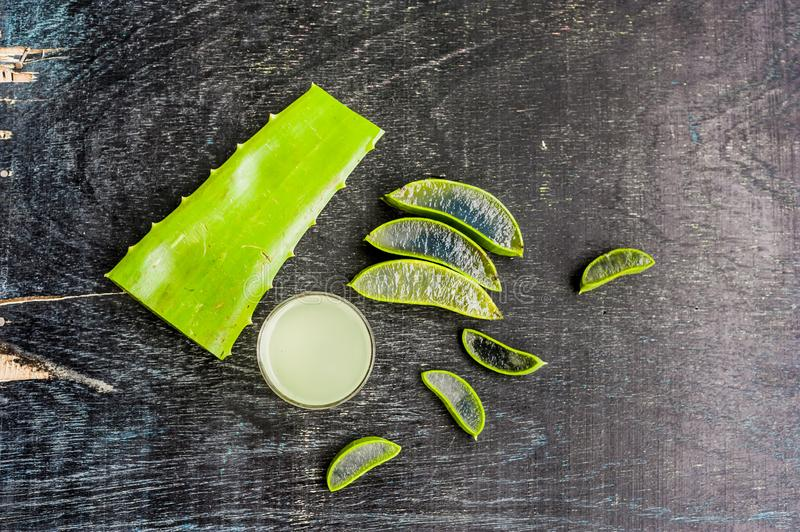 Aloe vera pieces and aloe gel in the glass on an old dark wood background Organic cosmetics concept. Natural cosmetics concept royalty free stock photography