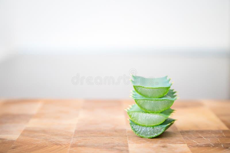 Aloevera-Betriebsscheiben gestapelt auf einander auf hölzernem Hintergrund mit Raum für Text stockfotografie