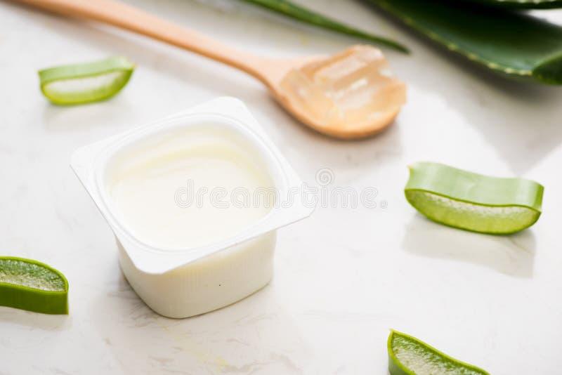 Aloevera-Jogurt mit frischen Blättern auf einem Holztisch lizenzfreies stockbild