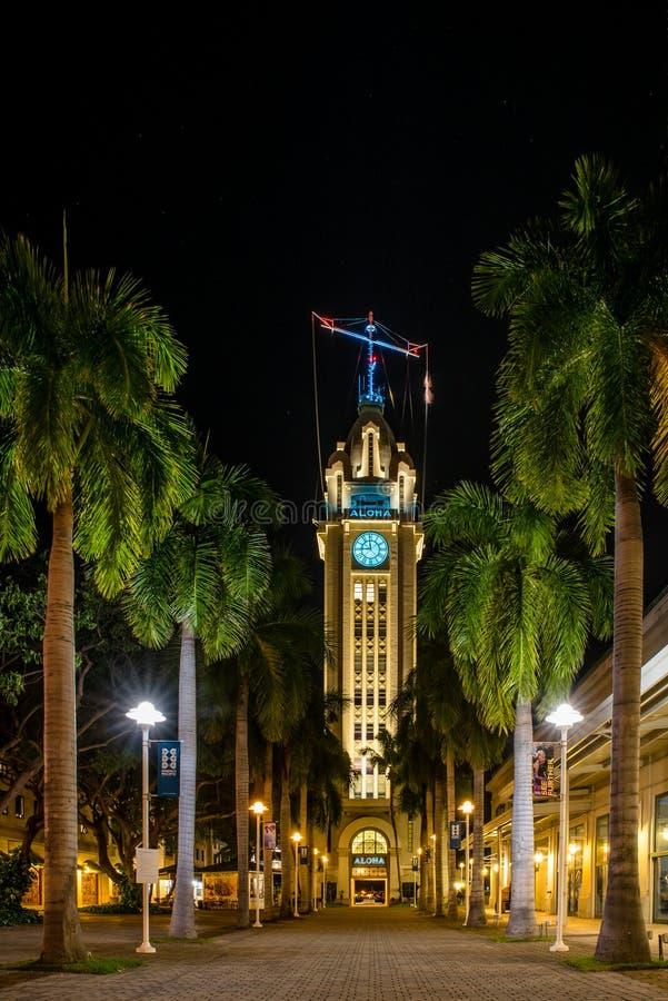 Aloha башня осветила вверх вечером с путем выровнянным с пальмами стоковые изображения rf
