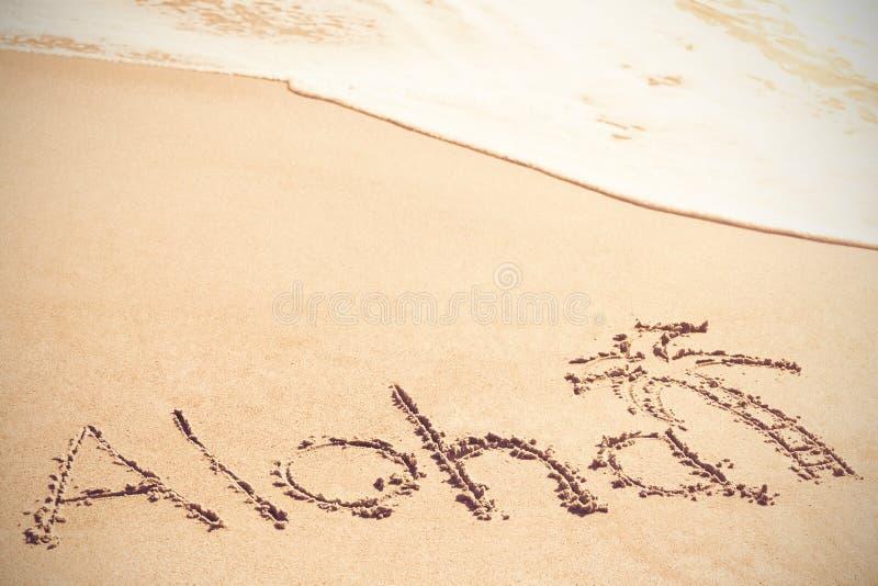Aloha texto escrito na areia com palmeira fotografia de stock