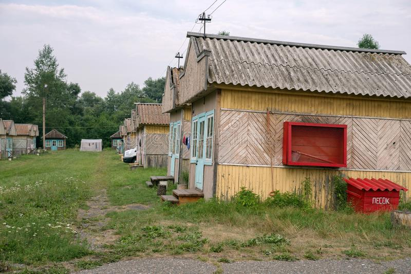 Alojamento de madeira do turista do verão com uma placa com meios da prevenção de incêndios no local de acampamento de Iskra na v imagem de stock