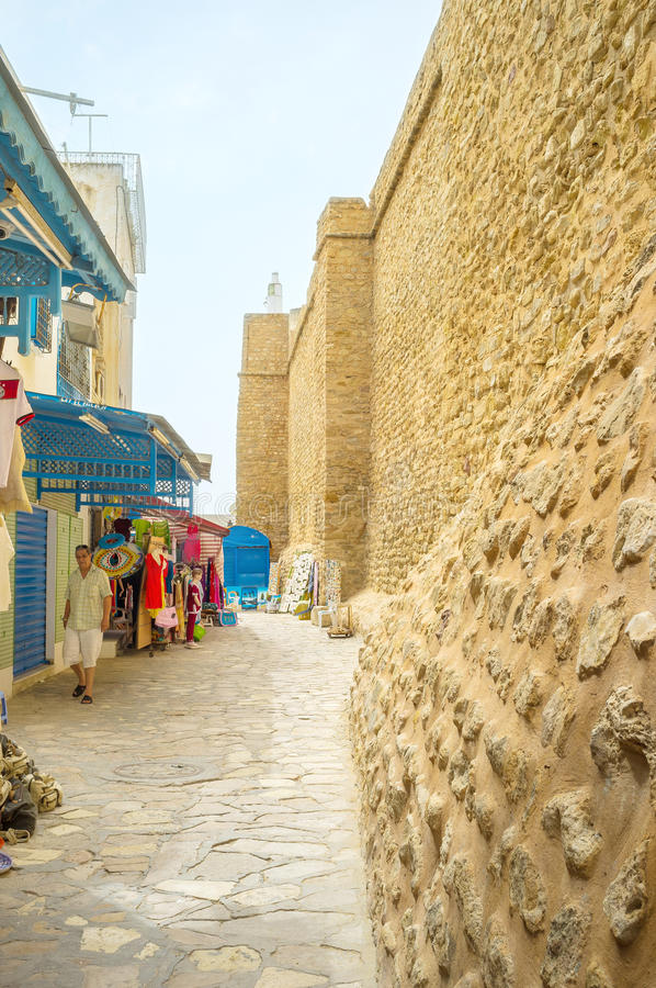 Alomg the fortress wall. HAMMAMET, TUNISIA - SEPTEMBER 6, 2015: The shopping street borthers with the old fortress wall, surrounding Medina, on September 6 in royalty free stock images