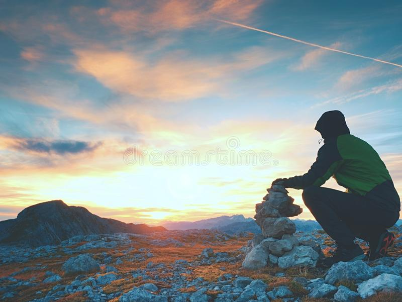 Alone adult man is stocking stone to pyramid.Alps mountain summit, evening sun at horizon. Mountains increased from humidity stock photos