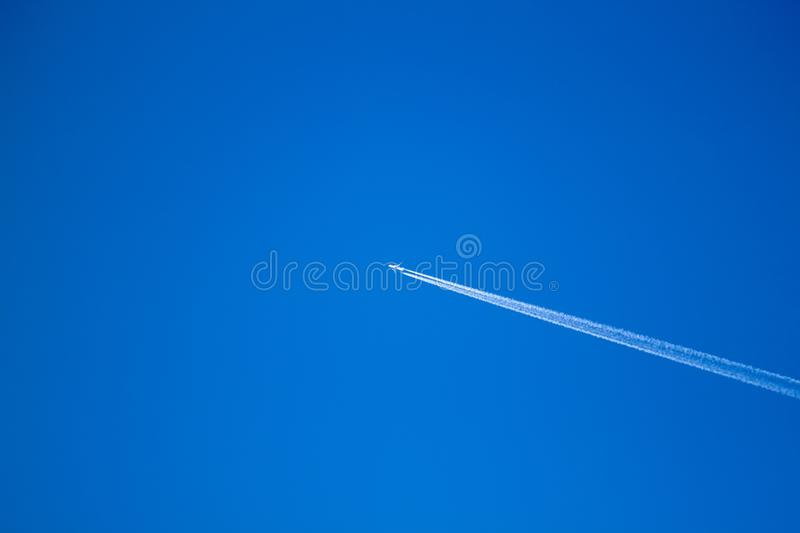 Alone airplane flying in clear blue sky with white condensation trails. High, jet, vapour, trace, travel, flight, atmosphere, aircraft, diagonal, passenger royalty free stock photos
