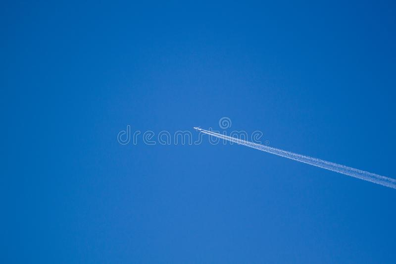 Alone airplane flying in clear blue sky with white condensation trails. High, jet, vapour, trace, travel, flight, atmosphere, aircraft, diagonal, passenger royalty free stock images