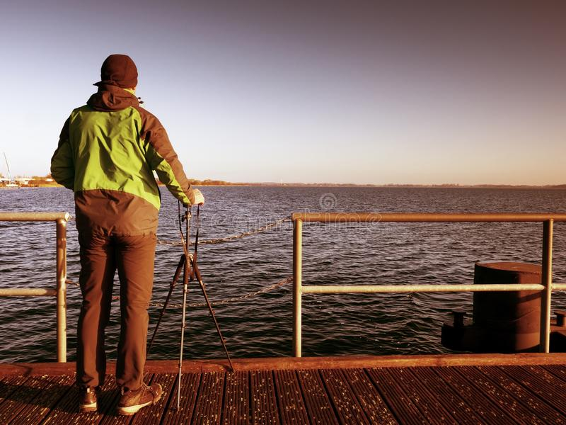 Alone artist on wooden bridge. Photographer with camera stock image