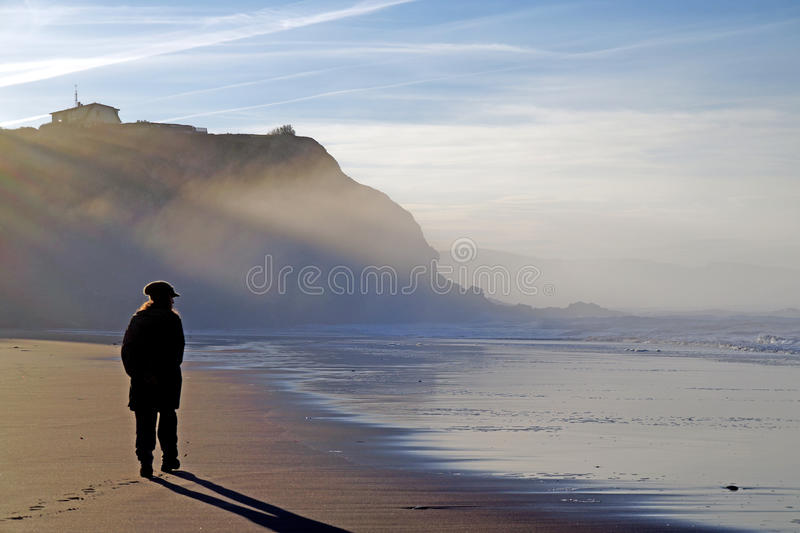 Alone on the beach. Walking alone on the beach stock image