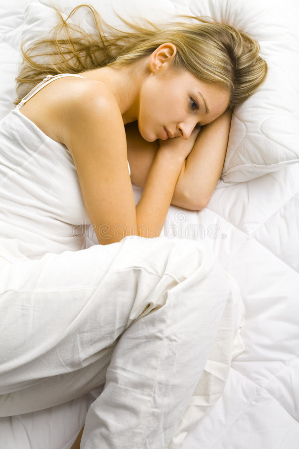 Alone in the bed. Young blonde woman lying alone in the bed. Looks dreamy