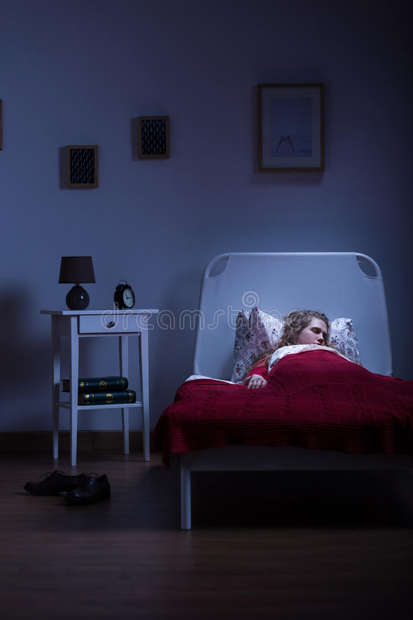 Alone in the bedroom. Young girl is sleeping alone in her apartament stock image