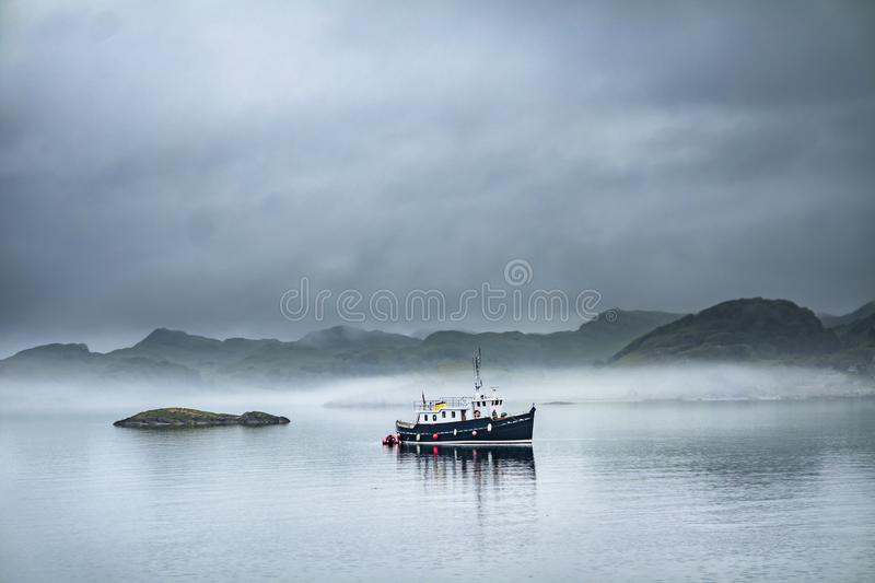 Alone boat driving through in the foggy sea in the scottish highlands. Alone boat driving through in the foggy sea in the Highlands of Scotland stock images