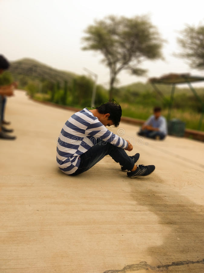 Alone boy sitting on the road royalty free stock image