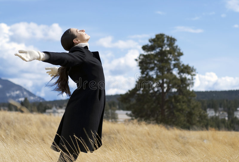 Alone in the field. Young woman standing alone in the field royalty free stock photography