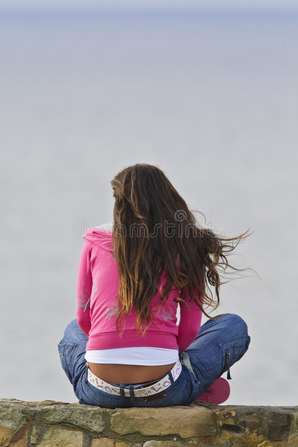 Alone girl looking at the sea stock photo