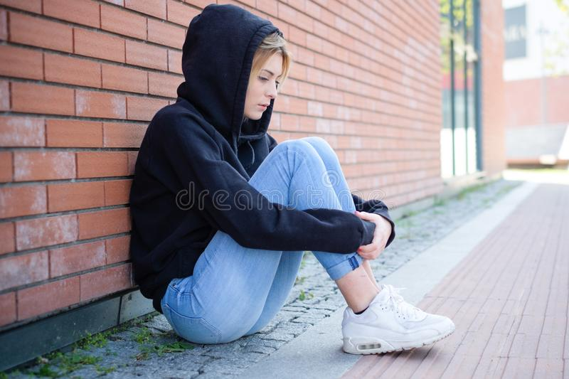 Alone girl portrait with hooded sweatshirt next urban street wall. Young girl portrait outdoor feeling alone and sad stock photo