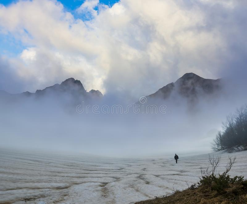 Hiker walking in a mist of mountain valley. Alone hiker walking in a mist of mountain valley royalty free stock photography