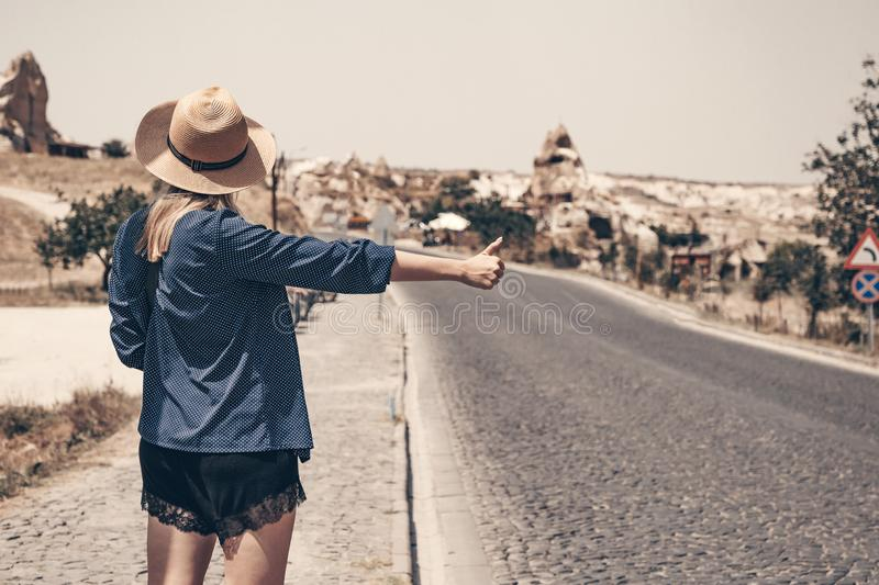 Alone hitchhiker girl in straw hat stands on the roadside. Arm with the thumb pointing upward. Mountains on the royalty free stock photo