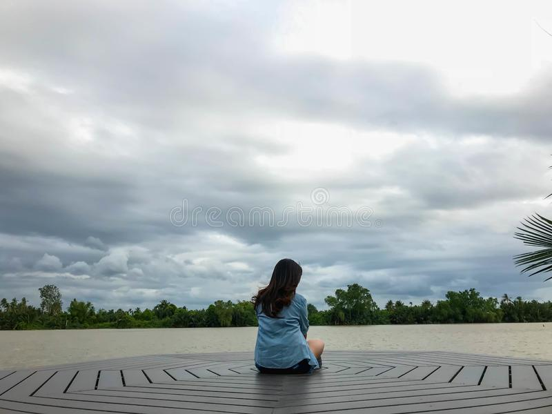 Alone lady sit on Waterfront royalty free stock photo