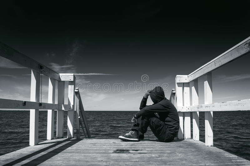 Alone Man at the Edge of Wooden Pier. Alone Man Sitting at the Edge of Wooden Pier, Looking at Water - Hopelessness, Solitude, Alienation Concept, Black and stock photography