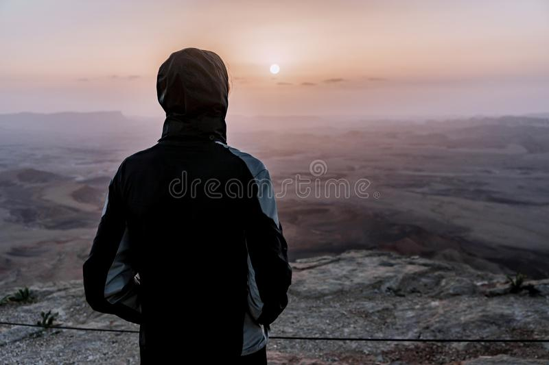 Alone man in israel negev desert admires the view of sunrise. Young male person stands on the edge of the cliff stock photos