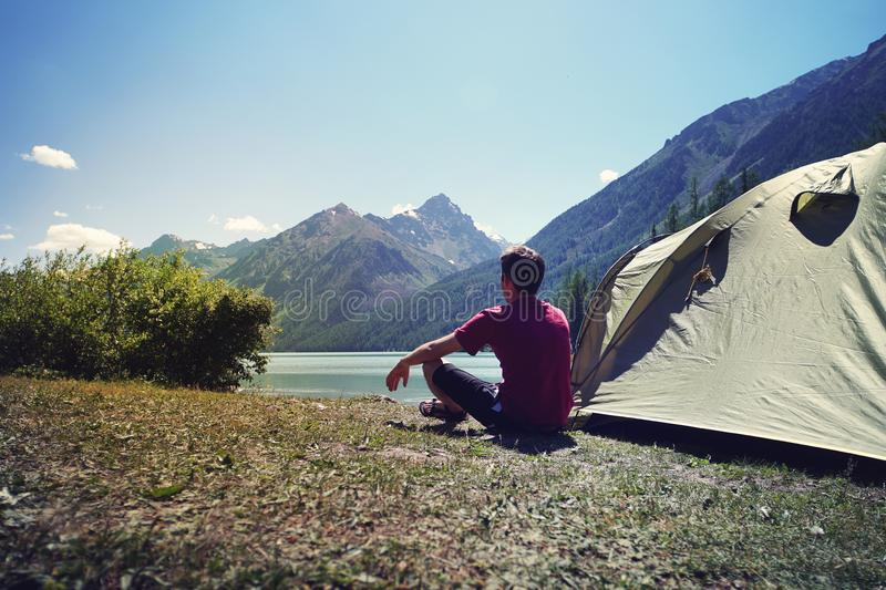Alone man travel near the lake mountain background, travel alone concept. Young tourist guy sitting after a green tent and looking royalty free stock images